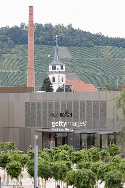 Tod's and Hogan store seen in front the vineyard and Martins chruch at Outletcity Metzingen on August 19 2016 in Metzingen Germany Metzingen is...