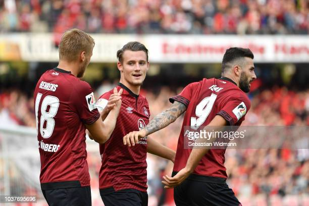 Toerles Knoell of Nuernberg celebrates scoring his teams second goal with teammates Hanno Behrens and Mikael Ishak during the Bundesliga match...