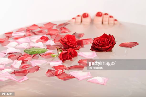 toes poking out of bath water with rose petals and roses floating in it - red tub photos et images de collection