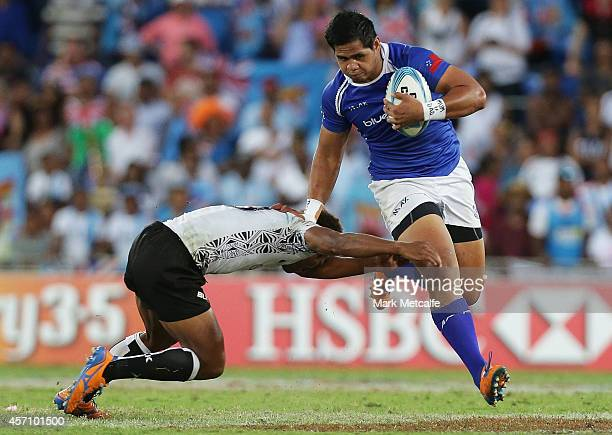Tofatuimoana Solia of Samoa is tackled by Osea Kolinisau of Fiji during the 2014 Gold Coast Sevens Cup final match between Fiji and Samoa at Cbus...