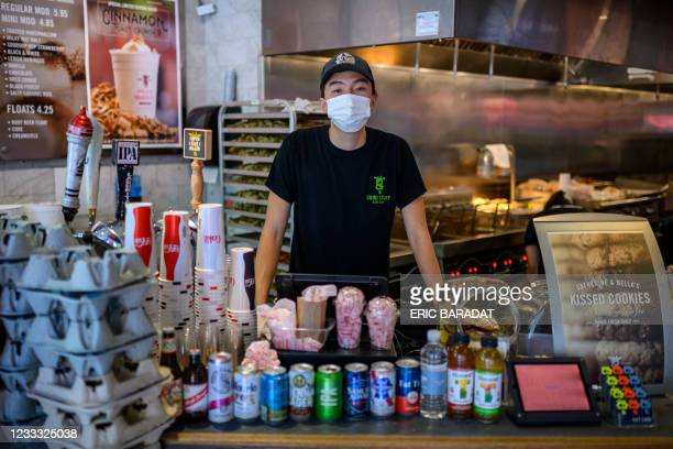 Togi, an 11th grade student at Wakefield High School, is seen at work in a fast food restaurant in Arlington, Virginia, on June 6, 2021. - When his...