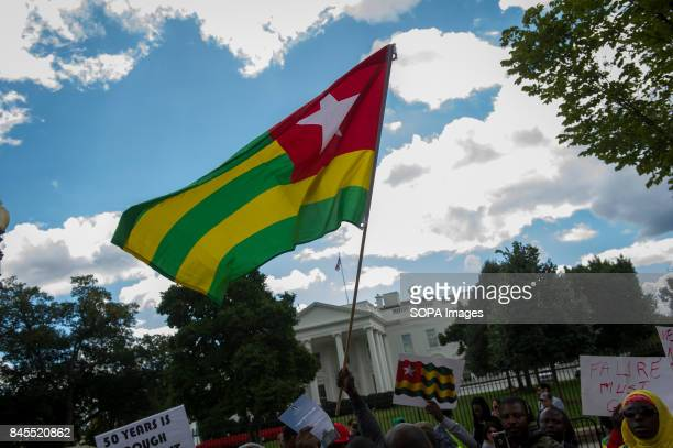Togo national flag seen in front of the White House. Protesters gather in front of the White House to protest against Togo's dictator Faure...