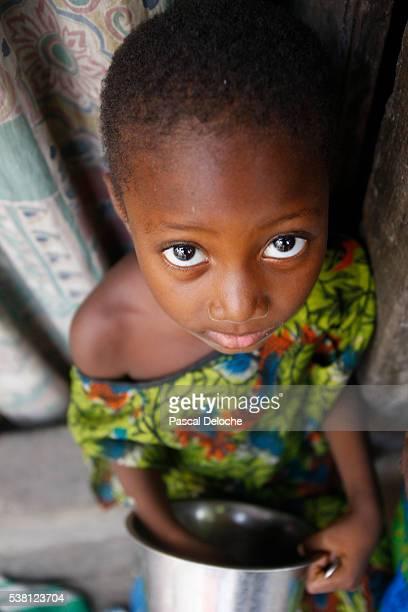 Togolese girl holding metal bowl