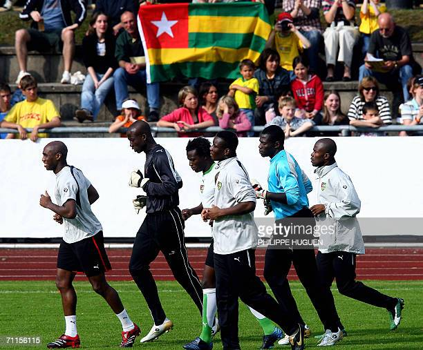 Togolese jog on the pitch past supporters bearing a national flag as they warm up for a team training session in The Allgustadion in Wagen 08 June...