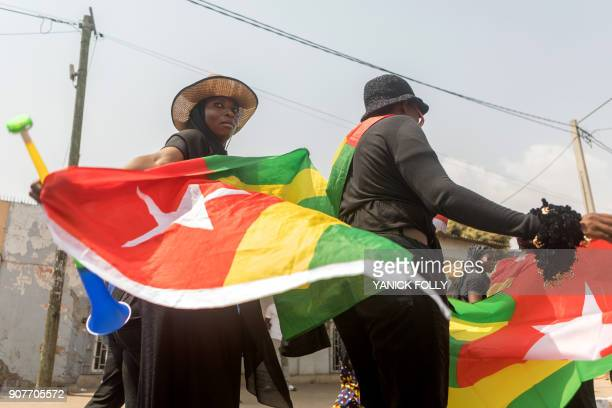 A Togolese woman dressed in black and holding the national flag takes to the streets of the capital Lome during a protest rally against Togo's...
