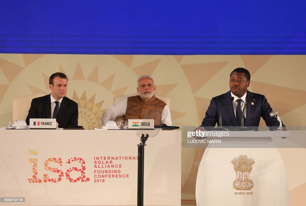 Togo's President Faure Gnassimbe delivers his speech next to French President Emmanuel Macron (L) and Indian Prime Minister Narendra Modi (C) during the founding conference of the International Solar Alliance in New Delhi on March 11, 2018. The International Solar Alliance (ISA) organizes more than 121 'sunshine' countries that are situated or have territory between the Tropic of Cancer and the Tropic of Capricorn, with the aim of boosting solar energy output in an effort to reduce global dependence on fossil fuels. / AFP PHOTO / Ludovic MARIN