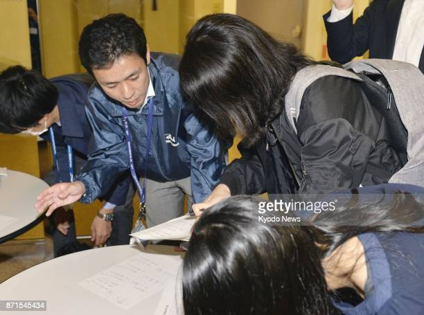A Toho Air Service Co official is questioned by reporters in Tokyo on Nov 8 after its helicopter crashed the Gunma Prefecture village of Ueno...
