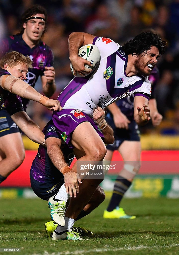 Tohu Harris of the Storm attempts to break the tackle of Ben Hannant of the Cowboys during the round 21 NRL match between the North Queensland Cowboys and the Melbourne Storm at 1300SMILES Stadium on July 30, 2016 in Townsville, Australia.