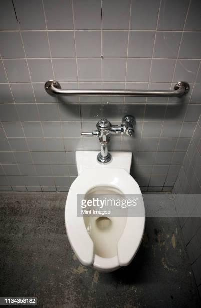 toilet bowl in a tiled restroom - cuvette photos et images de collection