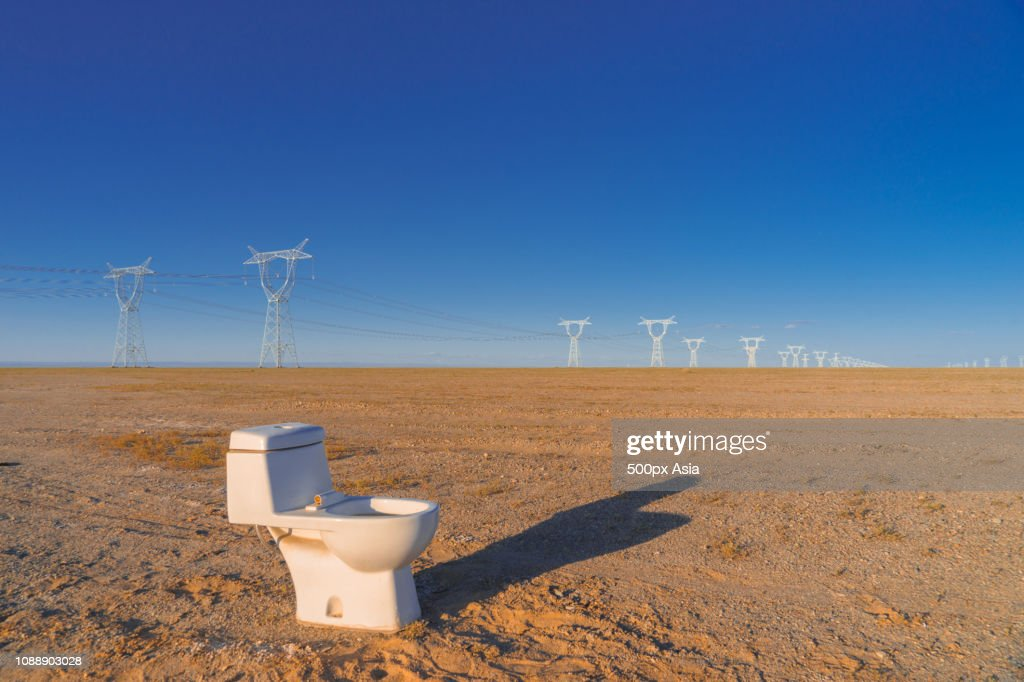 Toilet in barren field with power lines in background, Alxa League, Inner Mongolia Autonomous Region, China : Stock Photo