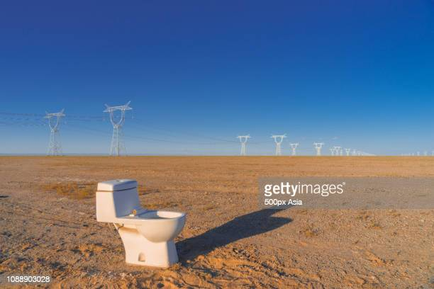 toilet in barren field with power lines in background, alxa league, inner mongolia autonomous region, china - image stockfoto's en -beelden