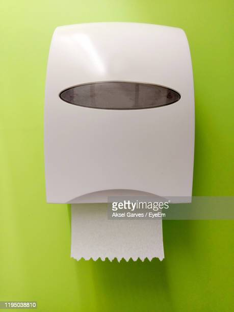 toilet paper hanging from machinery in wall - aksel garves stock-fotos und bilder