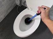 Toilet repair by hand Plumbing.A plumber uses a plunger to unclog a toilet.Toilet Plunger.