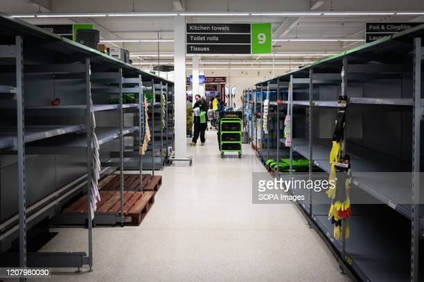 Toilet roll shelves left empty as an employee tries to replenish with the few rolls left in the store during the corona pandemic Despite advice from...
