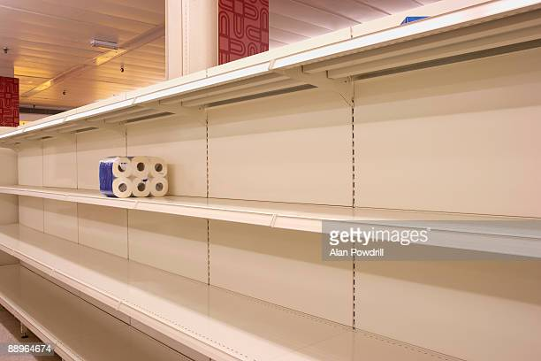 toilet rolls on empty shop shelf - panic buying stock pictures, royalty-free photos & images