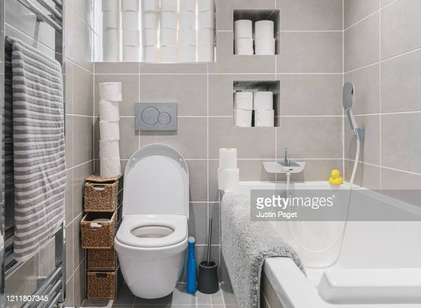 toilet with lots of toilet rolls - panic buying stock pictures, royalty-free photos & images