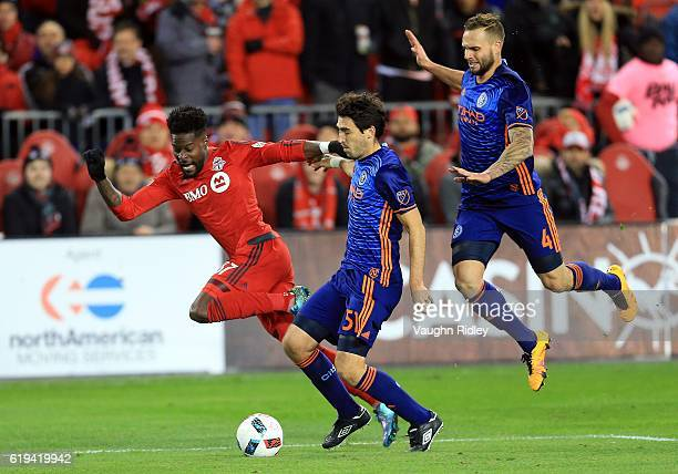 Toisant Ricketts of Toronto FC battles for the ball with Andoni Iraola and Maxime Chanot of New York City FC during the second half of an MLS...