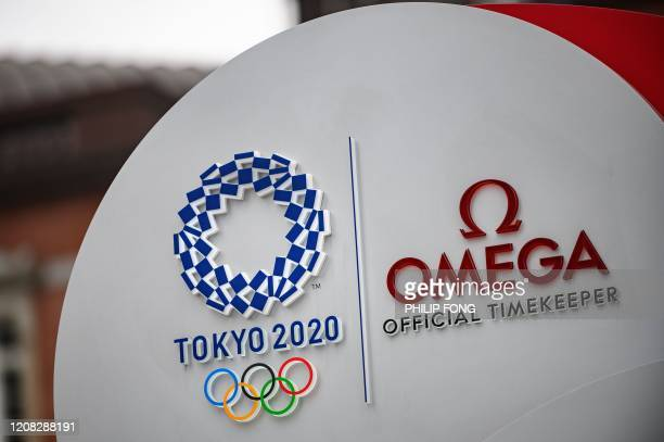 A Tokyo 2020 Logo is seen on the Tokyo Olympic Games countdown clock outside Tokyo Station in Tokyo on March 27 three days after the historic...