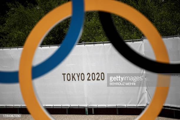 Tokyo 2020 logo is seen through the Olympic rings in front of the Olympic Stadium in Tokyo on July 20, 2021 ahead of the Tokyo 2020 Olympic Games.