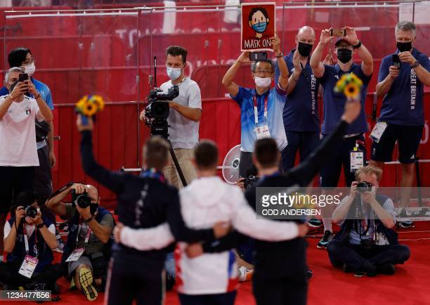 """Tokyo 2020 official holds for the athletes posing on the podium reading """"mask on"""" as bronze medallist Italy's Elia Viviani, gold medallist Britain's..."""
