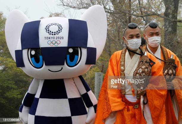 Tokyo 2020 Olympic Games mascot Miraitowa and Buddhist monks wearing protective face masks, amid the coronavirus disease pandemic, attend a ceremony...