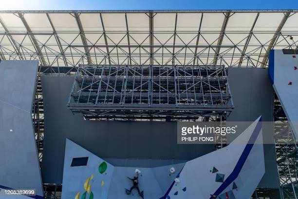 A Tokyo 2020 organizing staff climbs a wall during a bouldering test in Tokyo on March 6 2020