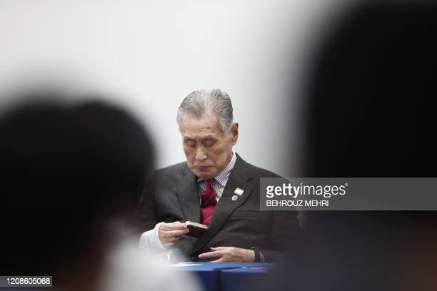 Tokyo 2020 president Yoshiro Mori checks his mobile phone during a press conference in Tokyo on March 30 2020 Postponed Tokyo Olympics to open July...