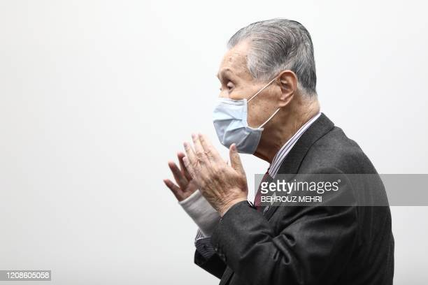 Tokyo 2020 president Yoshiro Mori puts on his face mask at the end of a press conference in Tokyo on March 30 2020 Postponed Tokyo Olympics to open...