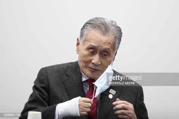 Tokyo 2020 president Yoshiro Mori removes his face mask as he attends a press conference in Tokyo on March 30 2020 Postponed Tokyo Olympics to open...