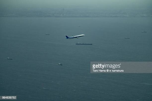Tokyo Bay and the airplane taking off Tokyo Haneda International Airport in Japan daytime aerial view from airplane