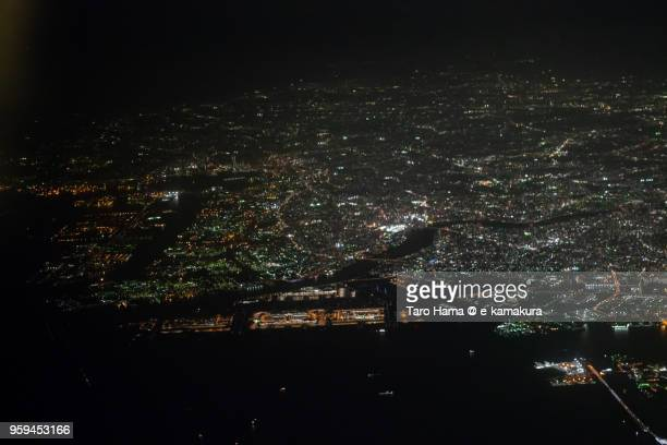 tokyo bay and tokyo haneda international airport in tokyo in japan night time aerial view from airplane - haneda tokyo stock photos and pictures
