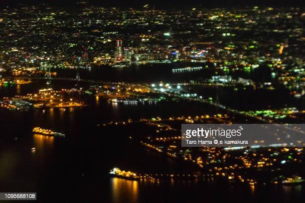 Tokyo Bay, illuminated factory area in Kawasaki city and Minato Mirai in Yokohama city in Kanagawa prefecture in Japan night time aerial view from airplane