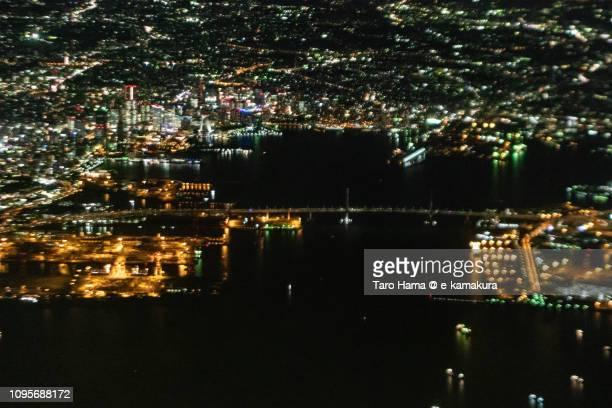 Tokyo Bay, Illuminated Minato Mirai in Yokohama city and Yokohama Bay Bridge in Kanagawa prefecture in Japan night time aerial view from airplane