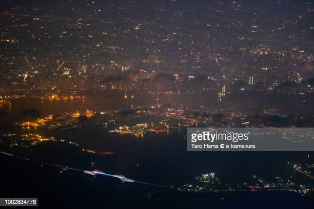 Tokyo Bay, Tokyo Rainbow Bridge and cityscape night time aerial view from airplane