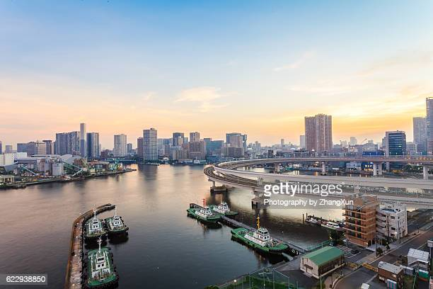 Tokyo bay with residential buildings and ships at sunset, Japan.