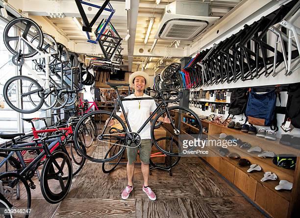 東京の自転車店のオーナーは、輪バイクを固定します。