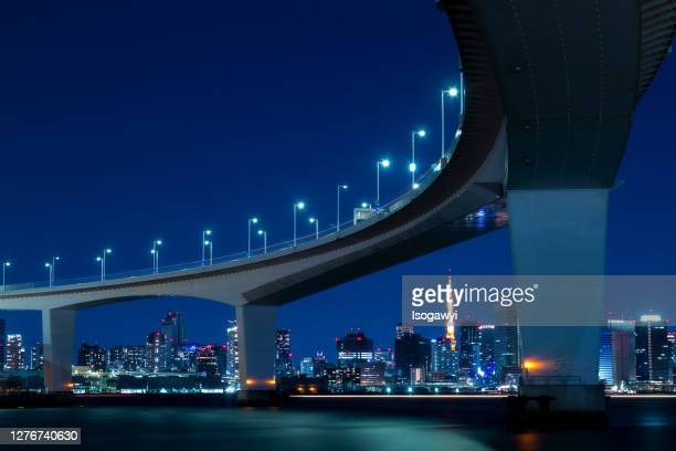 tokyo city skyline at night under the bridge of the metropolitan expressway - isogawyi stock pictures, royalty-free photos & images