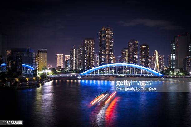 tokyo cityscape in tsukishima with skyscrapers and eitai bridge over sumida river at night, chuo ward, tokyo, japan. - 永代橋 ストックフォトと画像