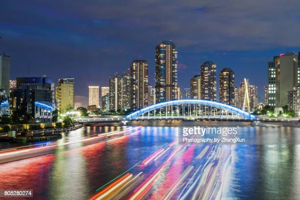 Tokyo cityscape in Tsukishima with skyscrapers and Eitai bridge over Sumida river at night, chuo ward, tokyo, japan.