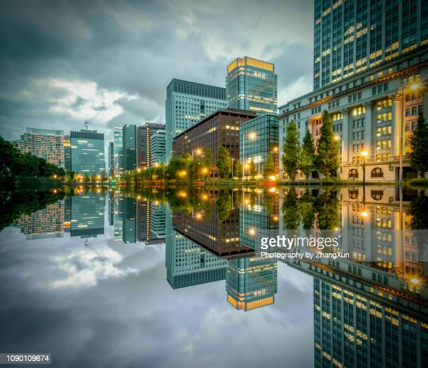tokyo cityscape with skyscrapers and office buildings illuminated reflection in hibiya, marunouchi, otemachi, chiyoda ward, japan at night. - imperial palace tokyo stock pictures, royalty-free photos & images