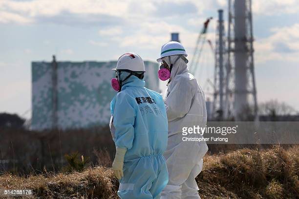 Tokyo Electric Power Co employee and a member of the media view the decontamination and reconstruction process at the Tokyo Electric Power Co's...