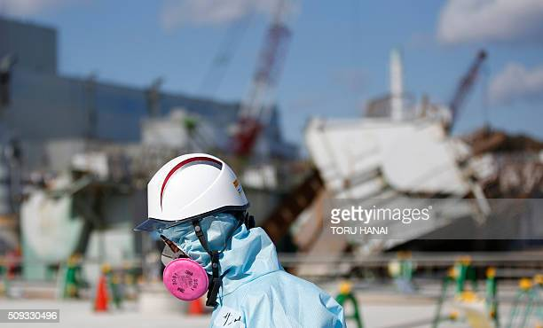 A Tokyo Electric Power Co employee wearing a protective suit and a mask walks in front of the No 1 reactor building during a media tour at TEPCO's...