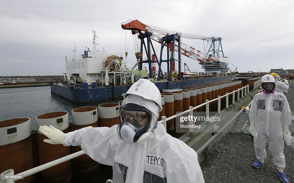 Tokyo Electric Power Co. (Tepco) employees wearing protective suits and masks walk past an impervious wall made of steel pipe sheet pile installed along the coast at the Fukushima Dai-ichi nuclear power plant in Okuma, Fukushima Prefecture, Japan, on Thursday, Nov. 7, 2013. Tepco, which returned to profitability in its first-half earnings report on Oct. 31, is handling an estimated 11 trillion yen ($112 billion) cleanup of the nuclear plant wrecked by an earthquake and tsunami in 2011. Photographer: Kimimasa Mayama/Pool via Bloomberg