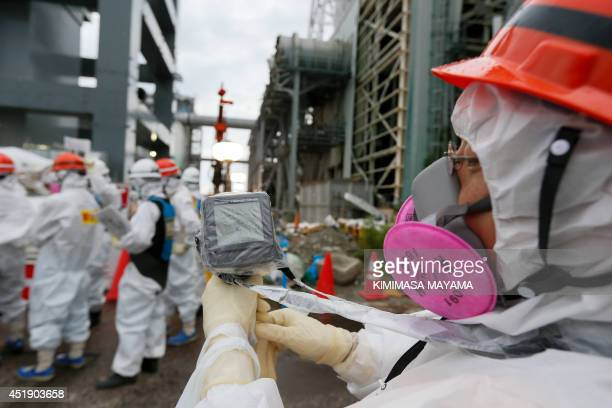 A Tokyo Electric Power Co's staff measures the radiation level as workers work on the construction of an ice wall at the tsunamicrippled Tokyo...