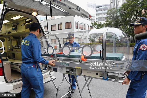 Tokyo Fire Department officers carry a capsule to take potential patients with Ebola during an exercise on November 11 2014 in Tokyo Japan No...