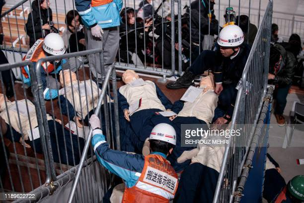 Tokyo Fire Department rescuers check on dummies of injured persons during a simulation disaster drill at the Ariake Gymnastics Centre a venue for the...