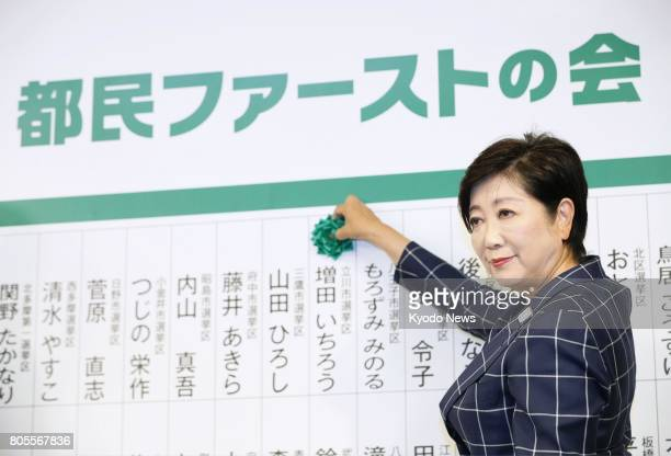 Tokyo Gov Yuriko Koike attaches a paper flower to the name of an elected member of her camp at the election results center of Tomin First no Kai in a...