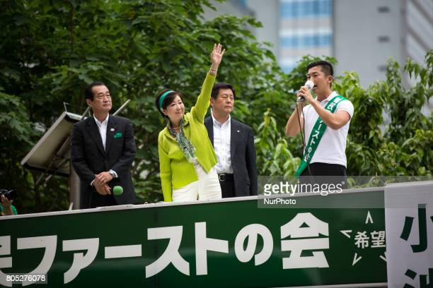 Tokyo Gov Yuriko Koike center who also heads the Tokyo Citizens First party waves her hands to voters from atop of a campaign van with party's...