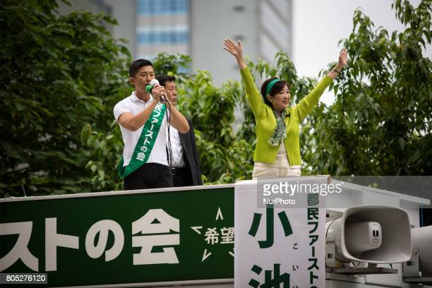 Tokyo Gov Yuriko Koike right who also heads the Tokyo Citizens First party waves her hands to voters from atop of a campaign van with party's members...