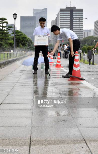 Tokyo government officials measure the surface temperature of a wet sidewalk in Tokyo on Aug 13 2018 An experiment was conducted to see how effective...